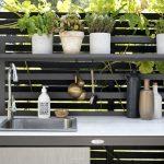 Udekøkken med vask i sort aluminium, med lamineret bordplade, aluminiums hylder og vaskskjuler i tekstil